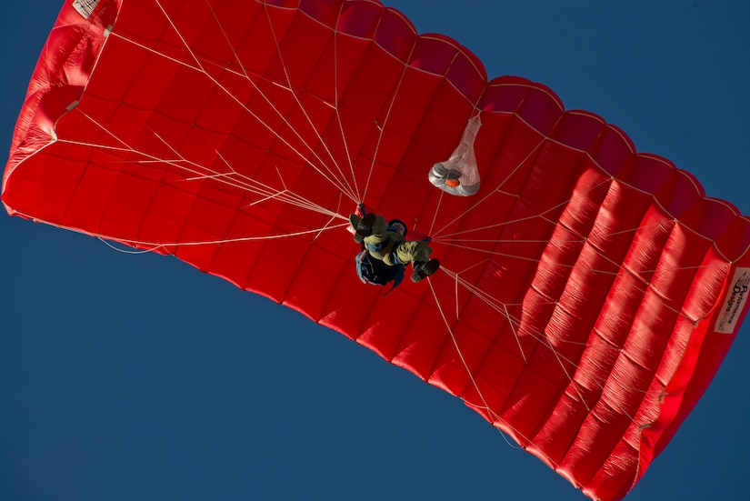 A U.S. Air Force Cadet prepares to land his initial parachute jump. Students are identified on their qualifying jumps by the red parachute canopies. (U.S. Air Force photo/Tech. Sgt. Bennie J. Davis III)