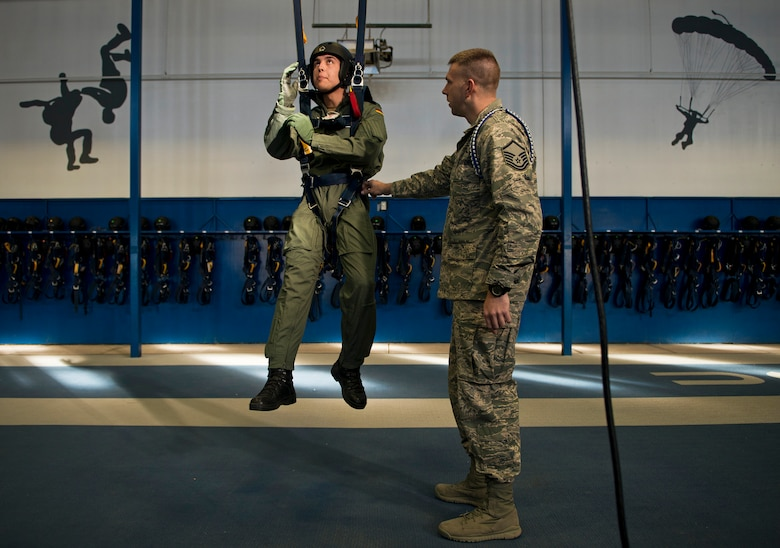 Master Sgt. David Siemiet, a jumpmaster with the Wings of Blue and AM490 instructor, prepares to teach a harnessed U.S. Air Force Academy International Cadet the proper techniques for troubleshooting a parachute canopy malfunction. AM490 is the only first-jump program in the world where students can make their first free-fall jump without assistance. (U.S. Air Force photo/Tech. Sgt. Bennie J. Davis III)