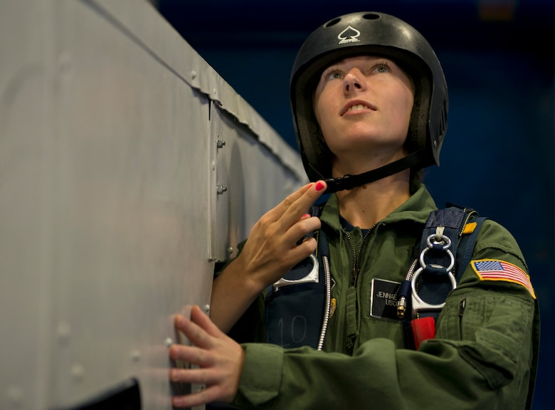"""U.S. Air Force Academy Cadet Jennae Stienmiller of the U.S. Coast Guard, receives the """"go"""" signal from her jump master as she stands in the door of a mock aircraft preparing to simulate a parachute free-fall jump. (U.S. Air Force photo/Tech. Sgt. Bennie J. Davis III)"""