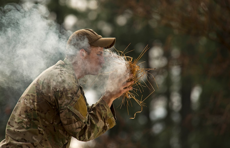 """Senior Airman Joseph Collett, a survival, evasion, resistance and escape instructor, teaches the """"bird's nest"""" technique of building a fire by igniting a small piece of flammable material with flint rocks and placing it inside a """"nest"""" of weeds while blowing air into the nest to help the flame grow. (U.S. Air Force photo/Tech. Sgt. Bennie J. Davis III)"""