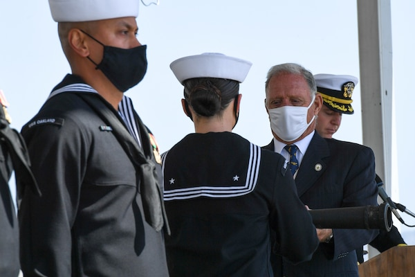 Mr. Greg Brazil sets the watch and passes the long glass to USS Oakland (LCS 24) Sailors during the ship's commissioning ceremony.