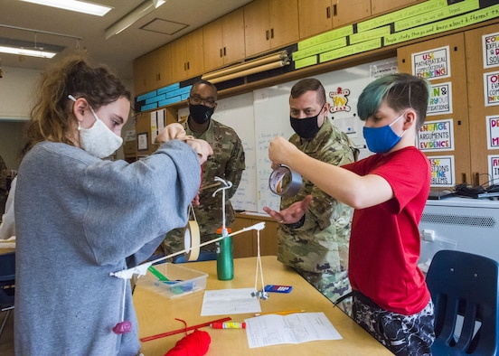 Two men in uniform assist two students, build a balancing contraption made from school supplies.