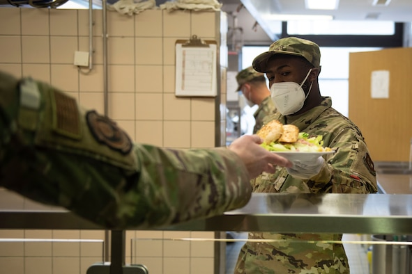 U.S. Air Force Senior Airman Andrew Logwood, 702nd Mission Support Flight dining facility storeroom manager, serves guests lunch in the dining facility, April 15, 2020, at the 702nd Munitions Support Squadron. During the COVID-19 pandemic, 702nd MUNSS MSF Airmen continued providing service, support and morale to 702 MUNSS Airmen by continuous training and listening to feedback from guests. (U.S. Air Force photo by Senior Airman Melody W. Howley)