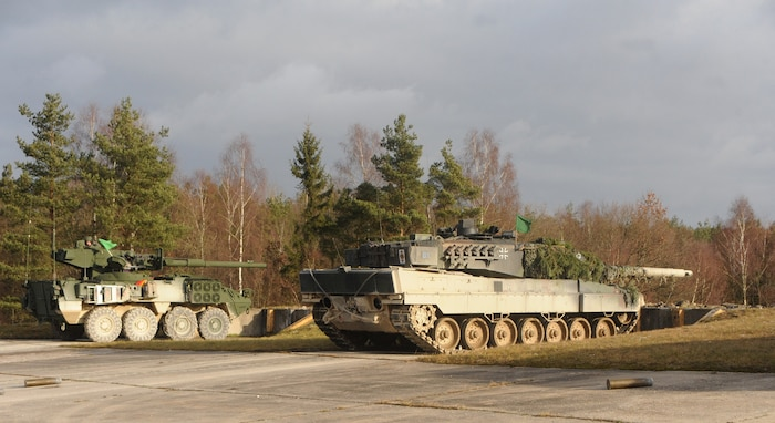 A U.S. Army Stryker Mobile Gun System vehicle and a German Bundeswehr Leopard 2 tank sit next to each other on the firing line in the Grafenwoehr Training Area during Operation Iron Panzer Dec. 8, 2011.