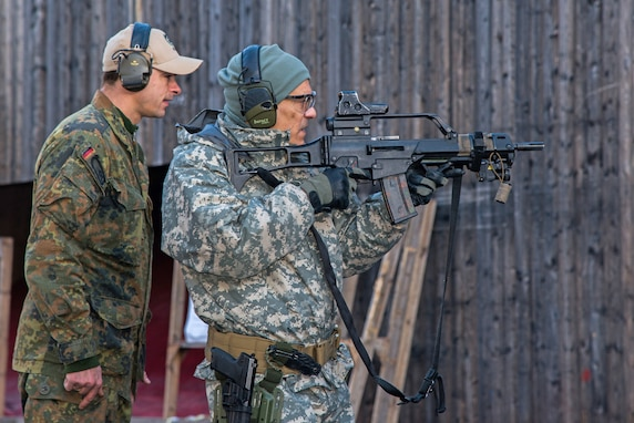 A German soldier (left) from the 2nd Company, Airborne Battalion 313 instructs a U.S. Army soldier from Special Operation Command as he fires Heckler & Koch G36 assault rifle from a standing firing position during his attempt to qualify for the German Schutzenschnur, the German Armed Forces Badge for Weapons Proficiency at a German/American partnership event at the Panzer Range Complex in Boeblingen, Germany.