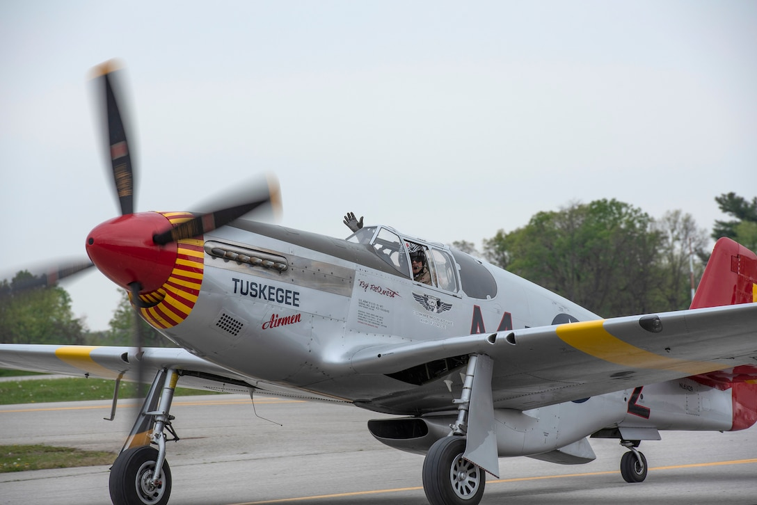 The pilot of a P-51 Red Tail waves while taxiing at Bowman Field following an aerial demonstration for the Thunder Over Louisville air show in Louisville, Ky., April 17, 2021. This year's event featured aircraft from multiple military and civilian agencies. (U.S. Air National Guard photo by Staff Sgt. Clayton Wear)