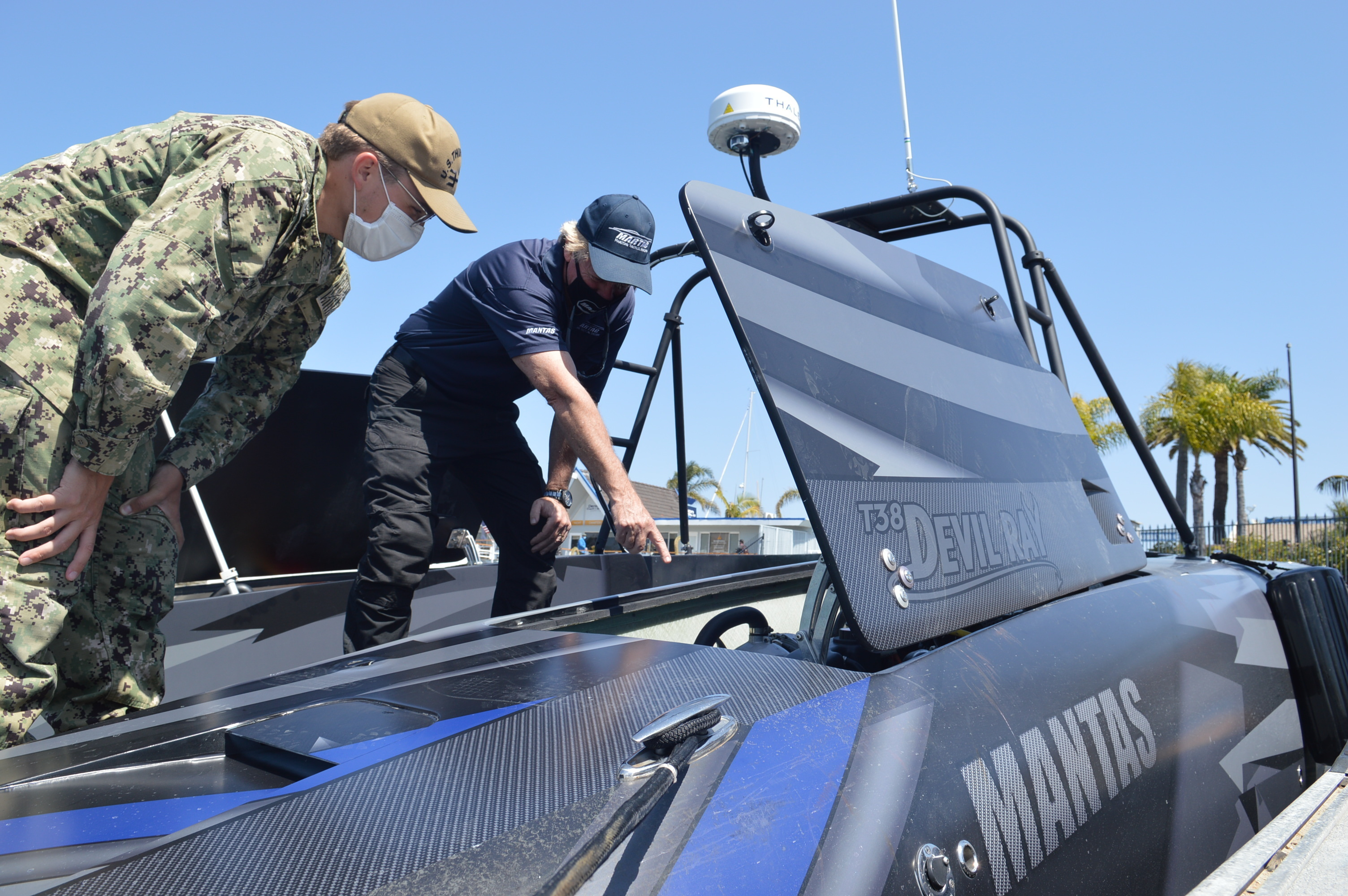 Petty Officer 3rd Class Casey Trietsch receives a tour and demonstration from Bruce Hanson aboard the MANTAS T38 Devil Ray unmanned surface vehicle.