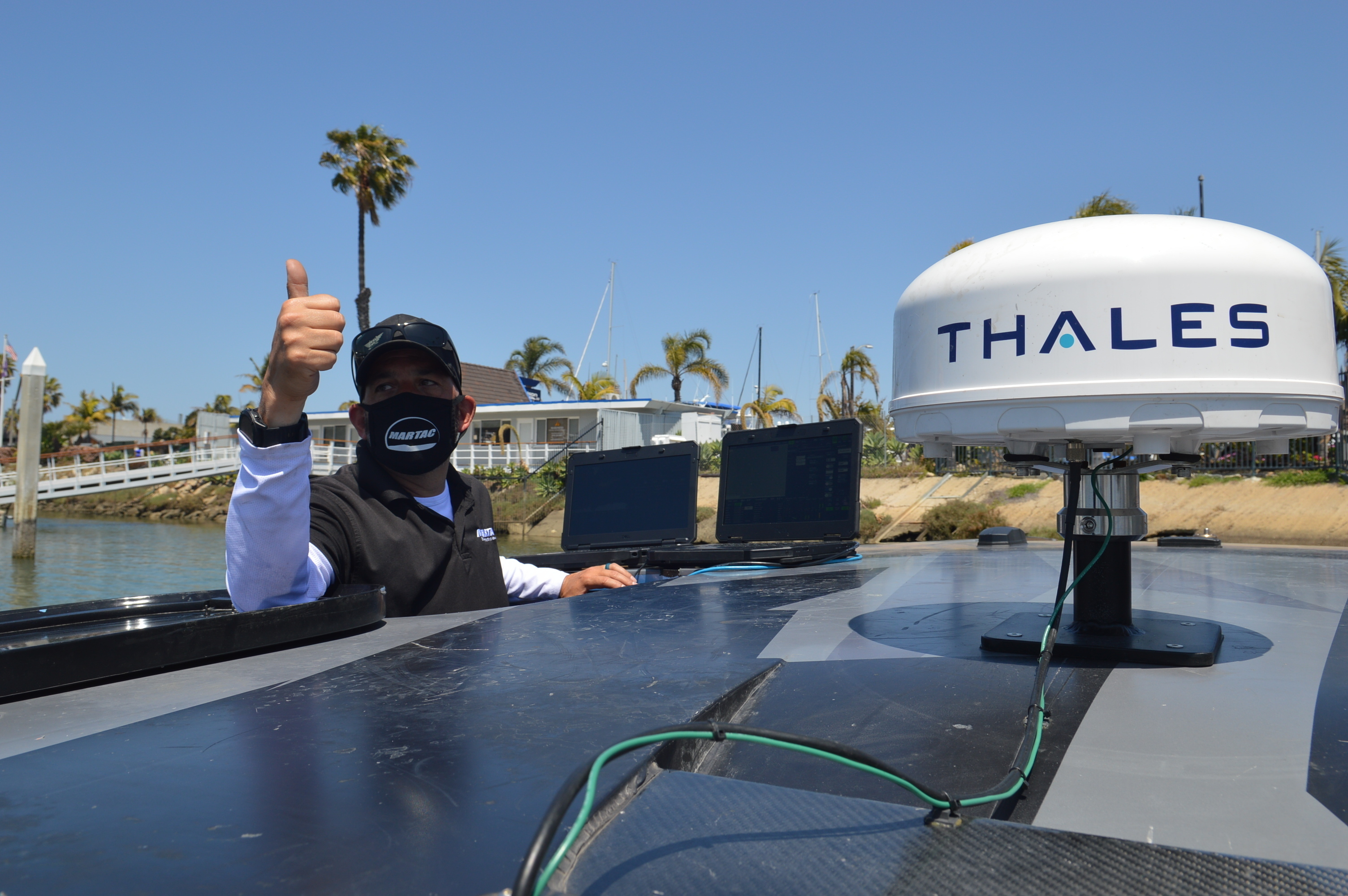 Chris Valdez signals during a pre-underway systems check aboard the MANTAS T38 Devil Ray unmanned surface vehicle at an operations demonstration.