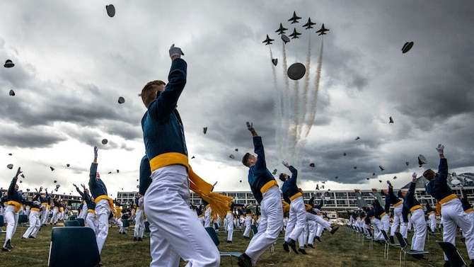 Spaced eight feet apart, United States Air Force Academy cadets celebrate their graduation as a team of F-16 Air Force Thunderbirds fly over the academy on April 18, 2020