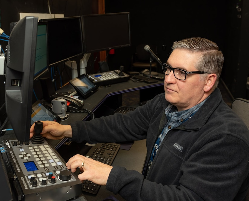 Photo of Grant Chyko sits at a computer console to set up one of the depots conference rooms for an upcoming meeting.  He's wearing black-framed glasses and a blue plaid shirt beneath a blue fleece jacket.