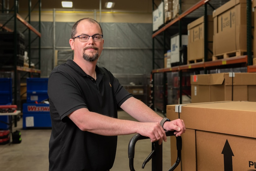 Photo of Andy Hrosovsky uses a hand truck to move equipment around a warehouse.  He is wearing black-framed glasses and a black short-sleeved polo shirt.