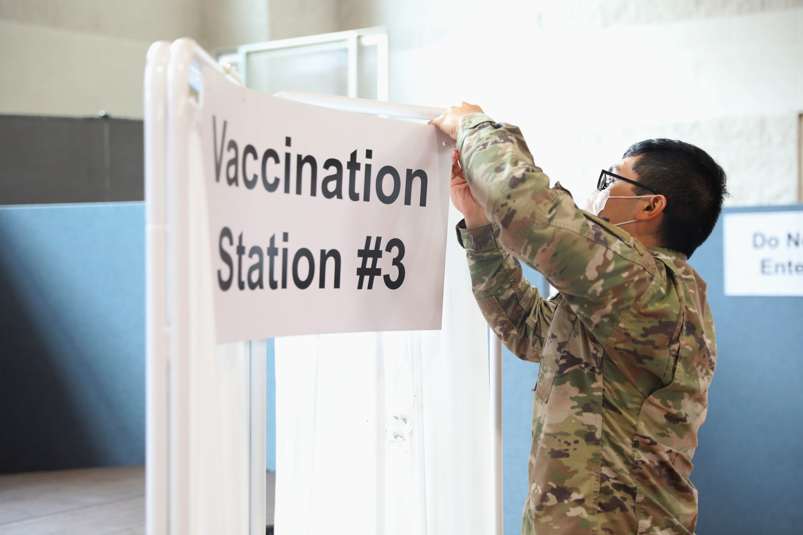 Service member takes down COVID-19 vaccination station signage