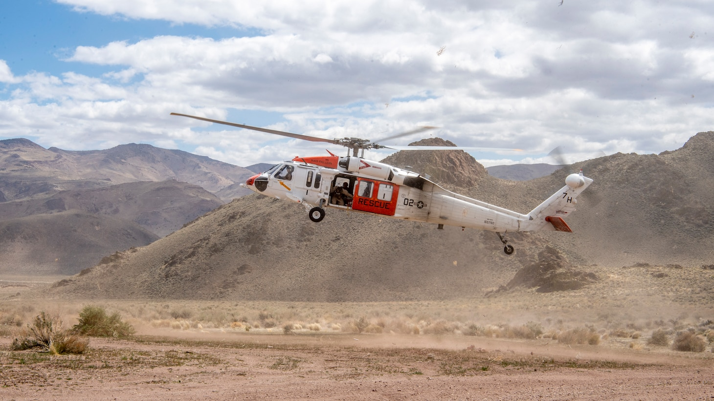 """An MH-60S Knighthawk helicopter, assigned to the """"Longhorns"""" of Helicopter Search and Rescue (SAR) Squadron, conducts a flight maneuver during a simulated SAR training exercise."""