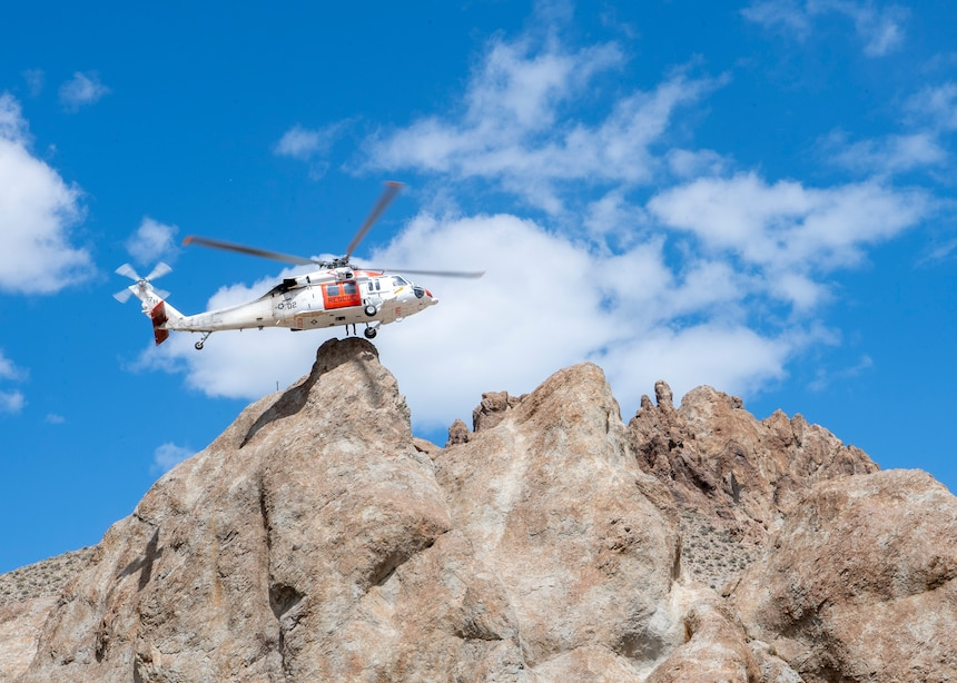 """An MH-60S Knighthawk helicopter, assigned to the """"Longhorns"""" of Helicopter Search and Rescue (SAR) Squadron, conducts a one wheel during a simulated SAR training exercise."""