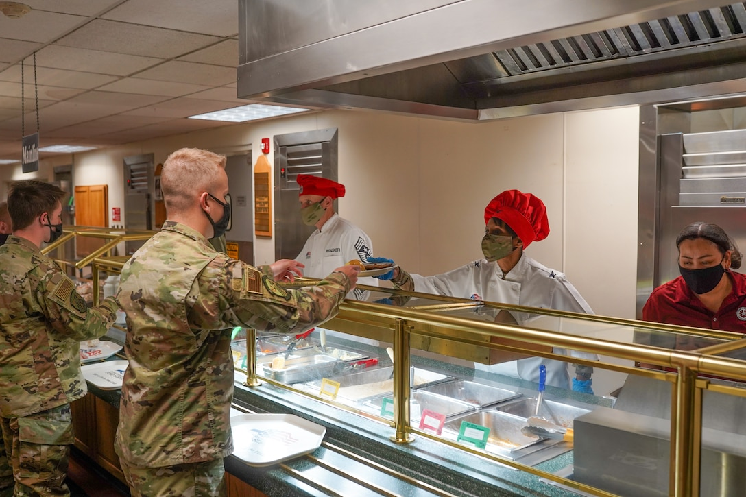 Chief Master Sgt. Christopher Walker (left), 75th Air Base Wing command chief, and Col. Jenise Carroll, 75th ABW commander, serve Air Force ROTC cadets lunch at the Hillcrest Dining Facility at Hill Air Force Base, Utah, April 9, 2021.