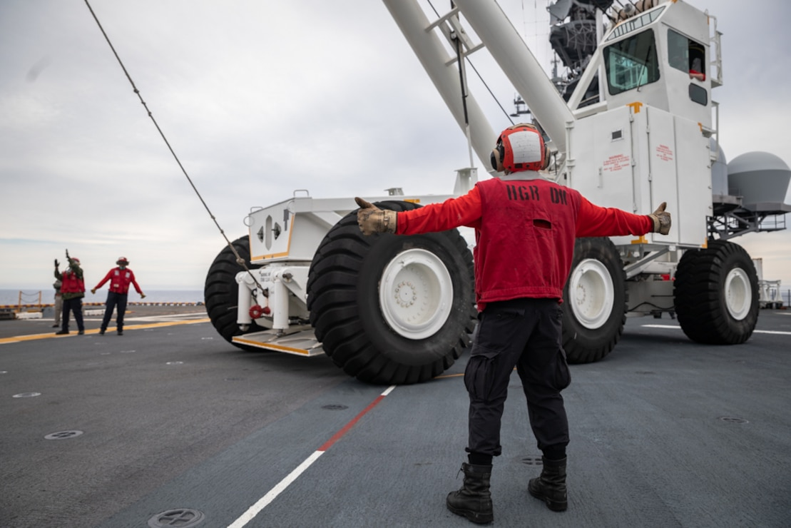 Aviation Boatswain's Mate 3rd Class Armando Contreras directs the driver of a crane on the flight deck of the Wasp-class amphibious assault ship USS Kearsarge (LHD 3).