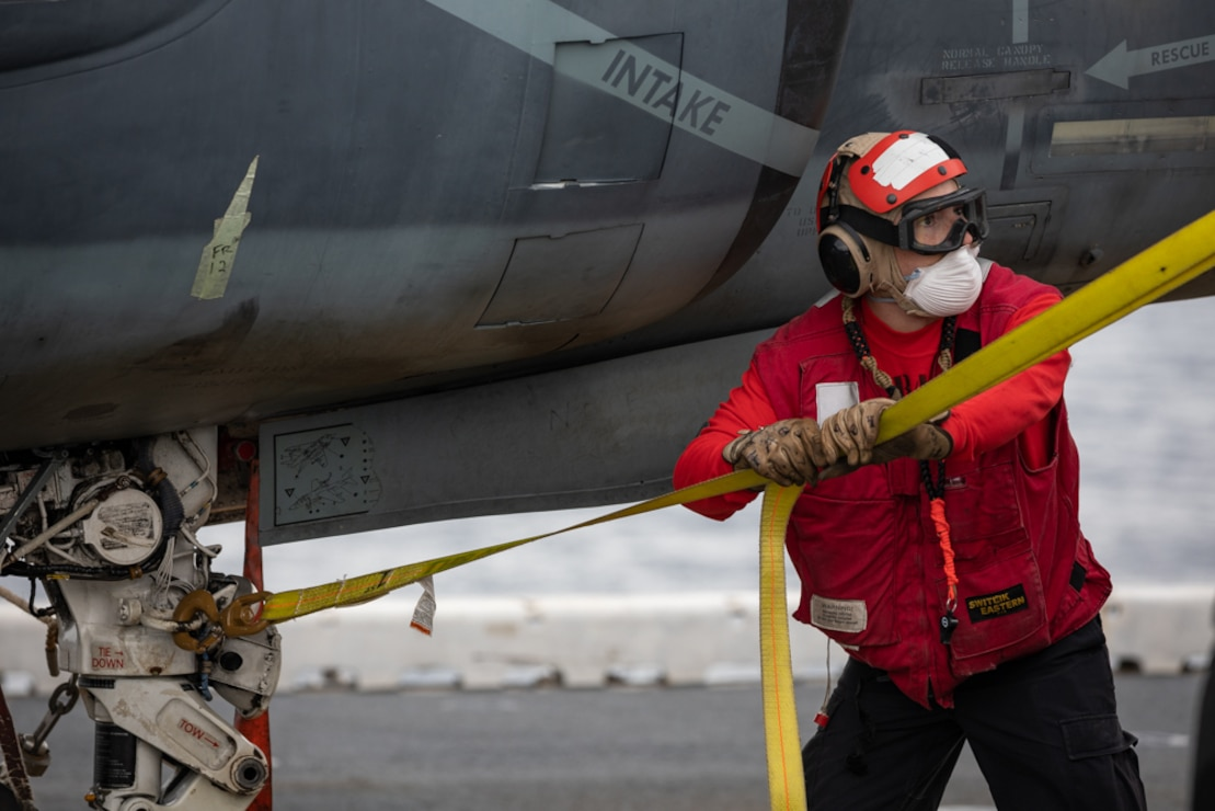 Aviation Boatswain's Mate 3rd Class Armando Contreras ties down a stabilizing line on a training AV-8B Harrier on the flight deck of the Wasp-class amphibious assault ship USS Kearsarge (LHD 3).