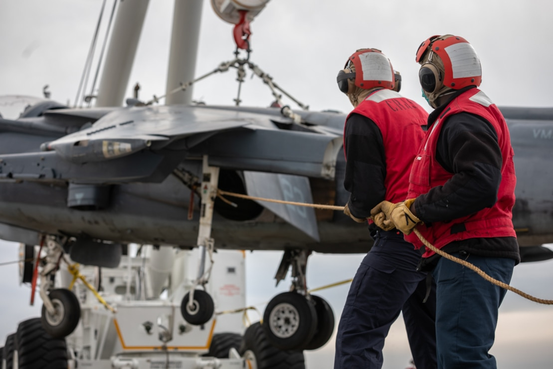 Aviation Boatswain's Mate (Handling) Airman Jacques Smith, right, and Aviation Boatswain's Mate (Handling) 3rd Class Lee Thomas, use lines to stabilize a training AV-8B Harrier during an immobile aircraft lifting evolution on the flight deck of the Wasp-class amphibious assault ship USS Kearsarge (LHD 3).