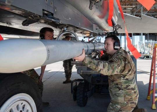 A Airman supports his three-man team in loading an Air Intercept Missile to an aircraft.