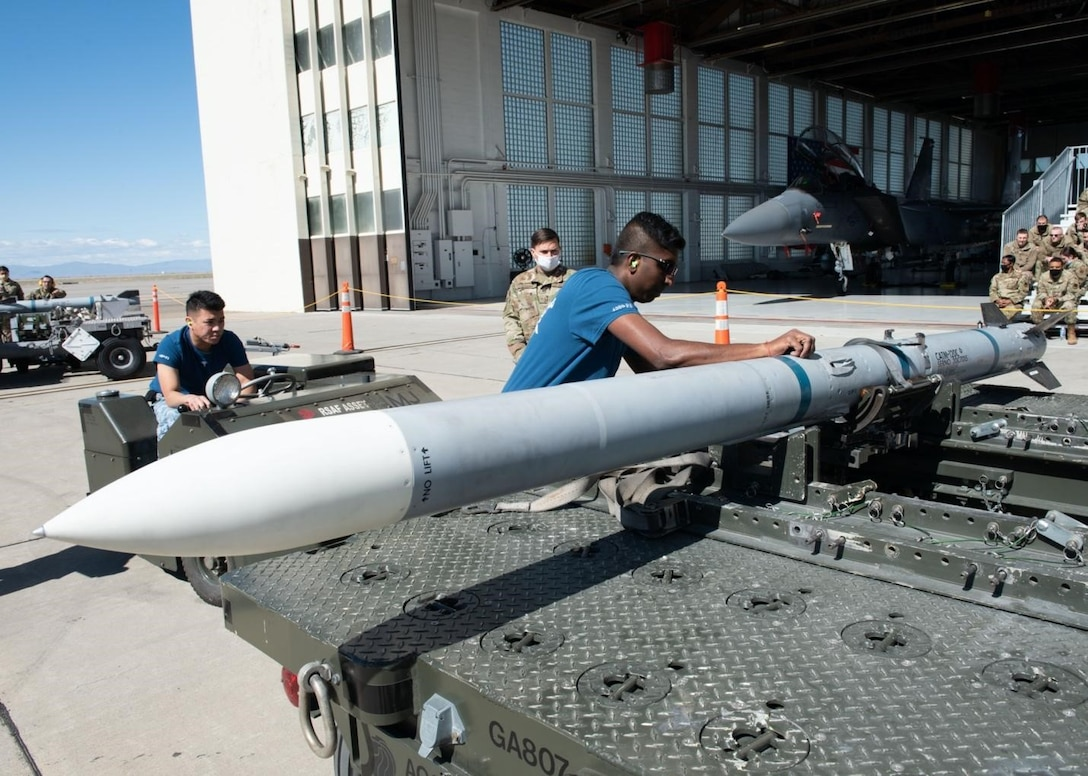 A Airman from the Republic of Singapore Air Force removes straps off an Air Intercept Missile.
