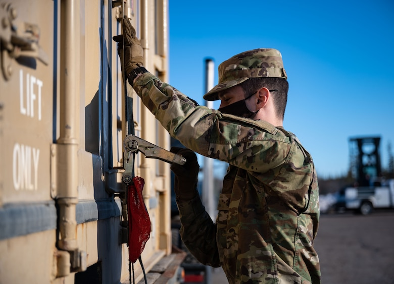 U.S. Air Force Airman 1st Class Mathew Bickford, a 354th Logistics Readiness Squadron ground transportation operator, secures a container during a munitions barge at Eielson Air Force Base, Alaska, April 16, 2021.