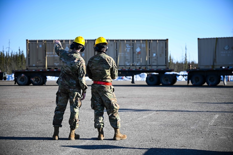 U.S. Air Force Airman 1st Class Kameron Page, left, a 354th Maintenance Squadron (MXS) munitions operations journeyman, and Airman 1st Class Carter Preston, a 354th MXS munitions stockpile apprentice, plan a shipping container unloading during a munitions barge at Eielson Air Force Base, Alaska, April 16, 2021.