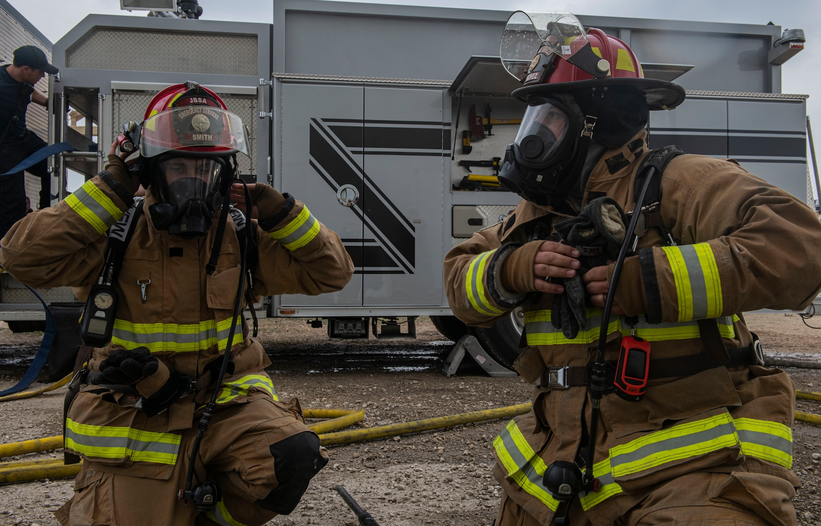 U. S. Air Force Staff Sgt. David Smith, left, and Andrew Sanchez, right, Joint Base San Antonio 902nd Civil Engineer Squadron lead firefighters, prepare for a forced entry scenario during a live fire training exercise, April 14, 2021, at Joint Base San Antonio-Randolph, Texas.