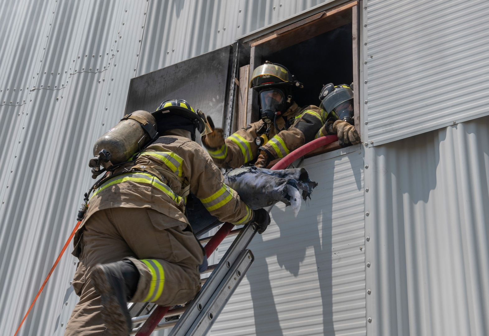 Joint Base San Antonio's 902nd Civil Engineer Squadron Fire Emergency Service members, and firefighters from Schertz and Cibolo fire departments, rescue a manikin from a building through a window during a live fire training exercise, April 14, 2021, at Joint Base San Antonio-Randolph, Texas.
