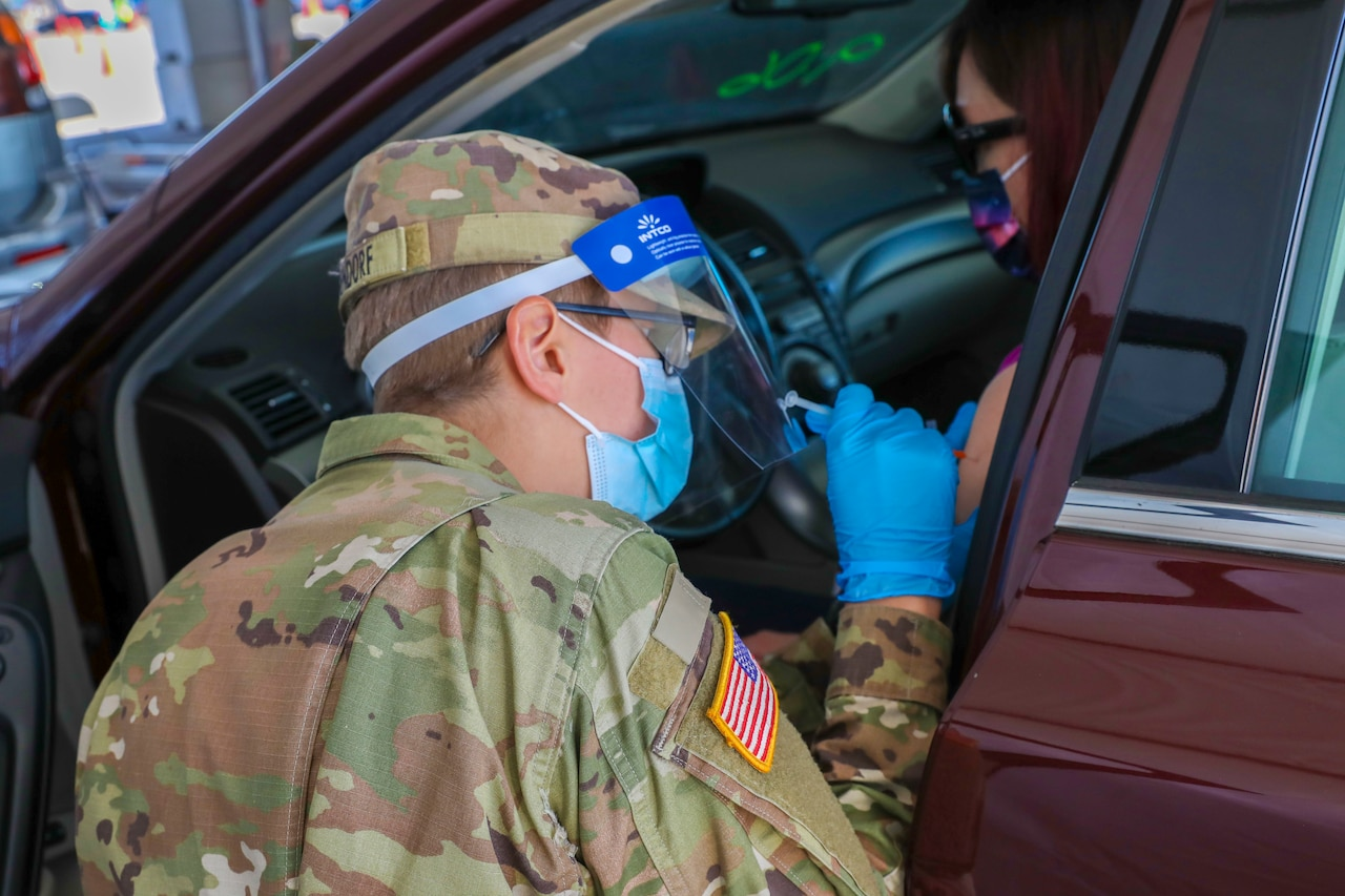 A person in military uniform kneels beside the driver's side of a passenger vehicle. She administers a vaccine to the driver.