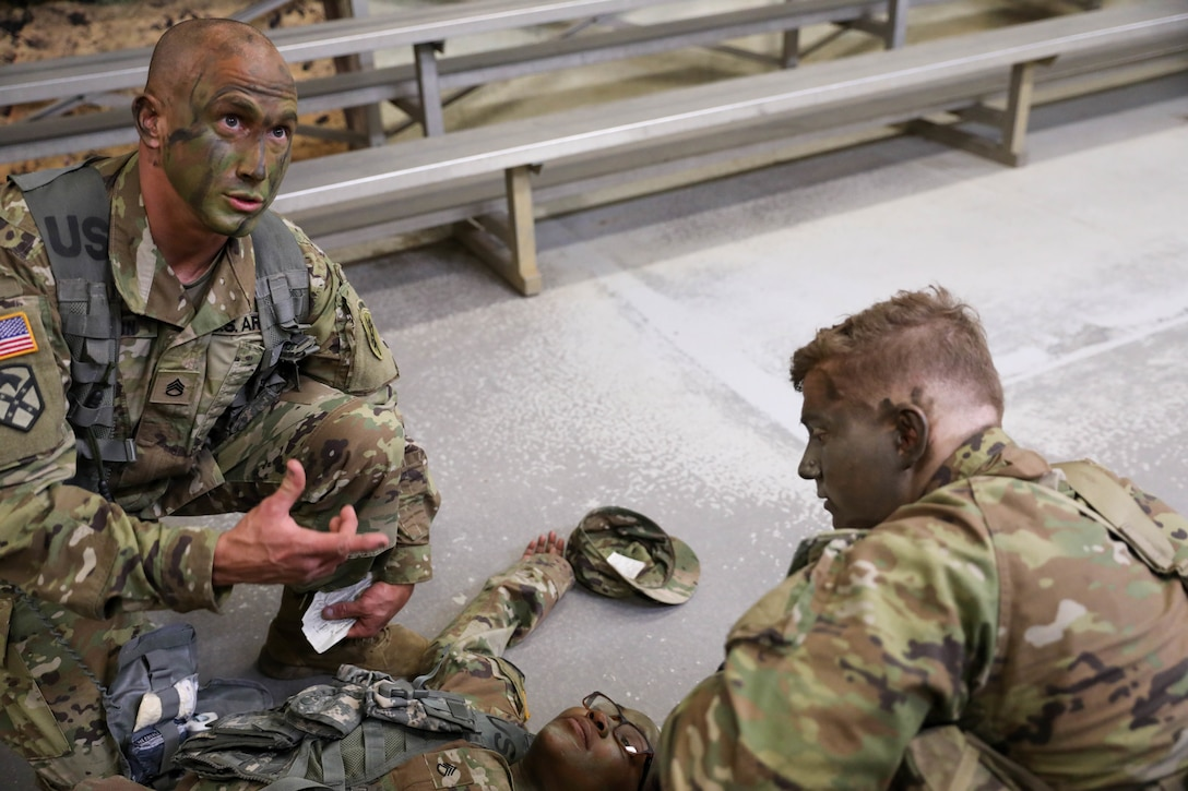 """U.S. Army Reserve Staff Sgt. Jonathon P. Chacon, civil affairs specialist with the 426th Civil Affairs Battalion, Upland, Calif., talks through evaluating """"casualty"""" Staff Sgt. Valery Valtrain, an intelligence analyst with the 151st Theater Information Operations Group, Fort Totten, N.Y., as team member, Spc. Timothy J. Lowitzer, a civil affairs specialist with the 1001st Civil Affairs and Psychological Operations Training Company, Trenton, N.J., looks on. The team ran through several drills prior to navigating the Medical Simulation Training Facility (MSFT) training lanes as part of the 2021 U.S. Army Civil Affairs and Psychological Operations Command (Airborne) Best Warrior Competition at Fort Jackson, S.C., held April 8-11. Competitors navigated the lanes individually, providing immediate combat life-saving measures to a simulated casualty while being evaluated on their medical evacuation techniques and casualty care skills. The USACAPOC(A) BWC enhances basic Soldier skills and individual readiness tasks needed to adapt to the ever changing operational environment. The top Soldier and Non-commissioned Officer who earn the title of """"Best Warrior"""" will go on to represent USACAPOC(A) at the U.S. Army Reserve Best Warrior Competition later this summer at Ft. McCoy, Wisconsin."""