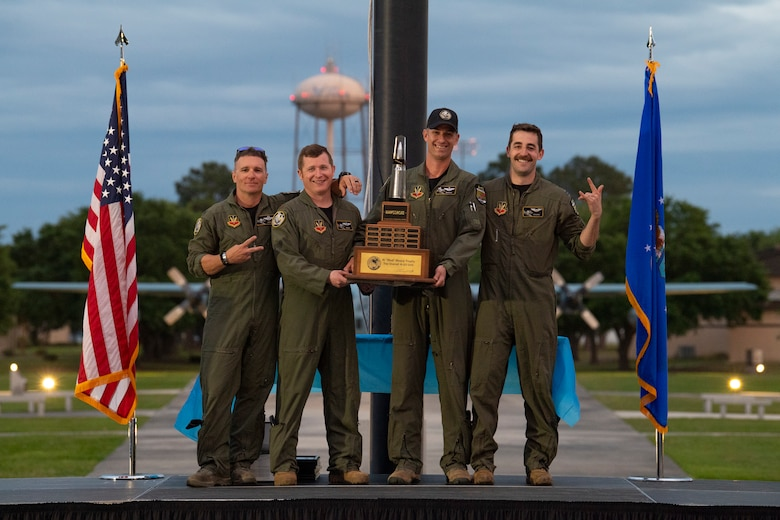 A photo of four Airmen posing, holding a trophy.