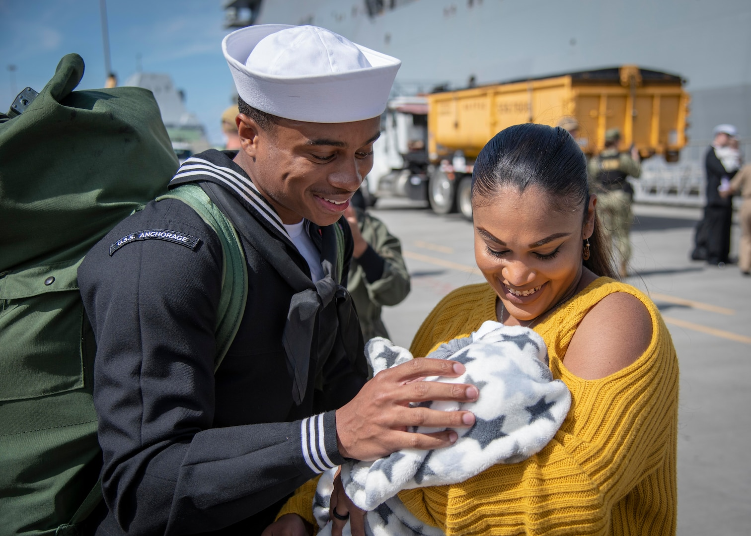 Service member looks at newborn in spouse's arms