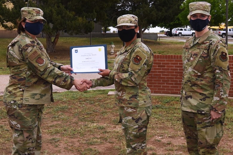 U.S. Air Force Col. Angelina Maguinness, 17th Training Group commander, presents Airman Brianna Jones, 315th Training Squadron student, the 17th TRG Student of the Month award for March 2021, outside of the Brandenburg Hall on Goodfellow Air Force Base, Texas, April 16, 2021. The 315th TRS's mission is to train, educate, and inspire the future intelligence, surveillance, and reconnaissance warriors through innovation. (U.S. Air Force photo by Senior Airman Abbey Rieves)