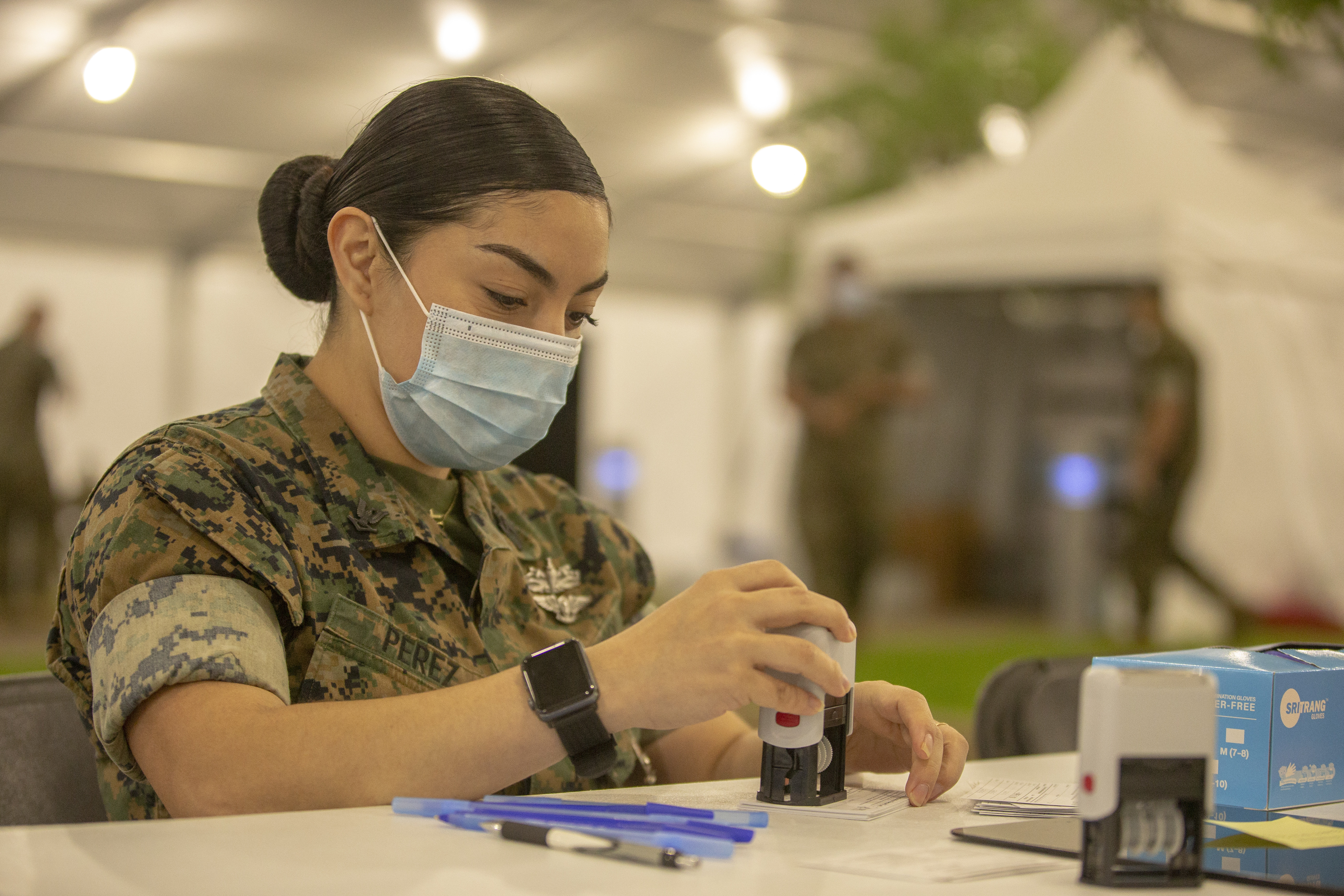 Hospital Corpsman 3rd Class Dora Perez assigned to 2d Marine Division, Camp Lejeune, North Carolina, prepares vaccination cards at the Memphis Community Vaccination Center in Memphis, Tennessee.