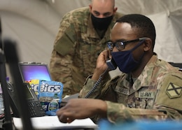 Alabama National Guard Spc. Anthony Hayes, working communications and information systems for the 1st Theater Sustainment Command's expeditionary command post validation exercise at Camp Arifjan, Kuwait, calls to follow up on a help ticket April 12, 2021, alongside Alabama National Guard Spc. Timothy Decker. The guardsmen, both deployed to Kuwait with the 115th Expeditionary Signal Battalion, manned the ECP's Joint Node Network and the new Tampa satellite system. (U.S. Army photo by Staff Sgt. Neil W. McCabe)