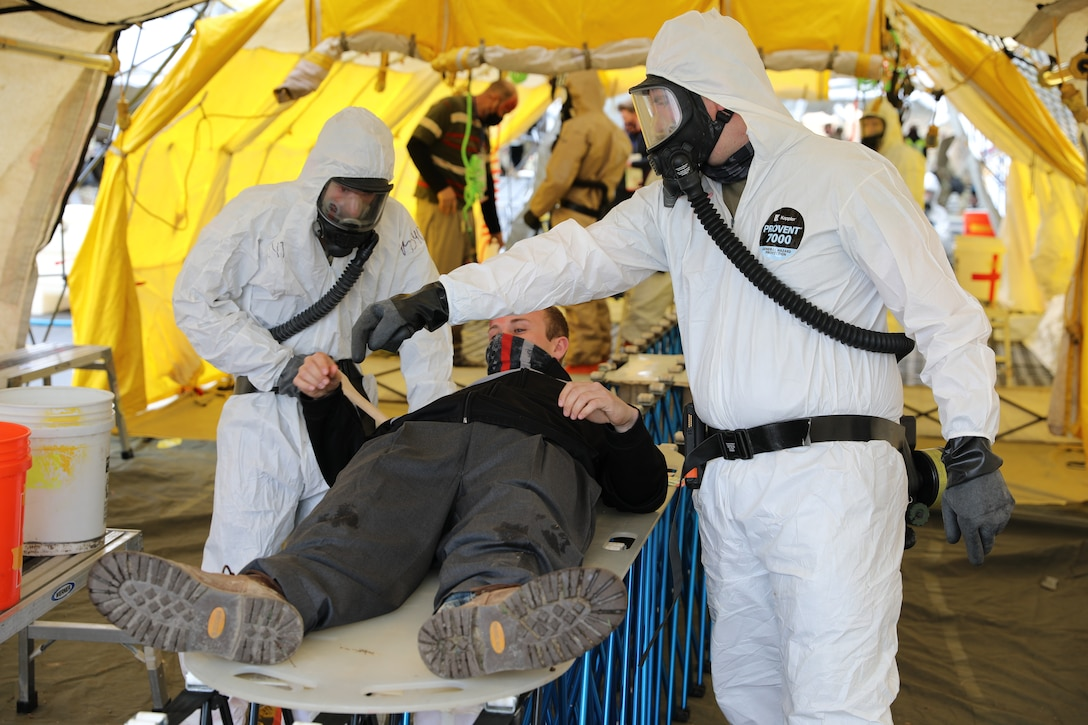 Soldiers from Alpha Company, 642nd Aviation Support Battalion of the New York Army National Guard, practice casualty decontamination with a civilian role-player during a Homeland Response Force collective training event in East Amherst, New York on April 17. The Solders are assigned as part of the decontamination element of the FEMA Region II HRF, tasked with response in the first hours and days of natural or manmade disasters. (Army National Guard Photo by Capt. Avery Schneider)