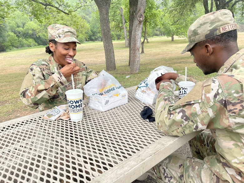 Tech. Sgt. Nessie McCray, 344th Training Squadron, and her son, Airman Basic Jaylen Netterville, 343rd Training Squadron, share lunch at Joint Base San Antonio-Lackland, Texas, April 15, 2021. Both look forward to graduating and beginning their new careers. (U.S. Air Force photo by Agnes Koterba)