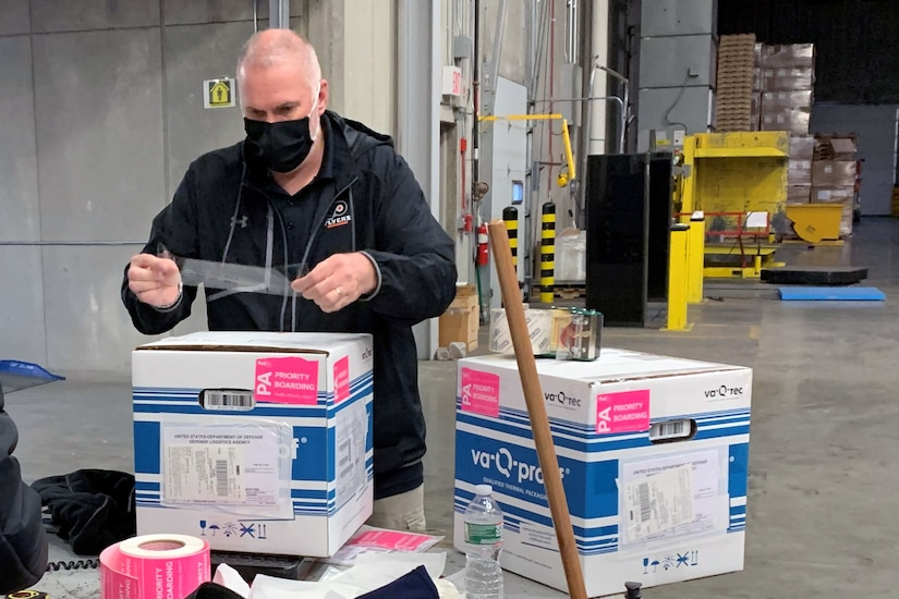 A man puts clear tape on a package.
