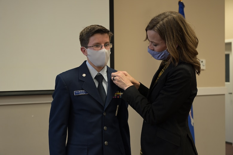 Golden Triangle Composite Squadron Civil Air Patrol cadet 2nd Lt. Matthew Carden, incoming cadet commander is pinned by his mother, Kristina Carden, during a change of command ceremony, Apr.1, 2021, on Columbus Air Force Base, Miss. Nationally there is almost 21,000 cadets and 33,000 senior members in numerous squadrons servicing the communities, state, and Nation as volunteers. (U.S. Air Force photo by Airman 1st Class Jessica Haynie)