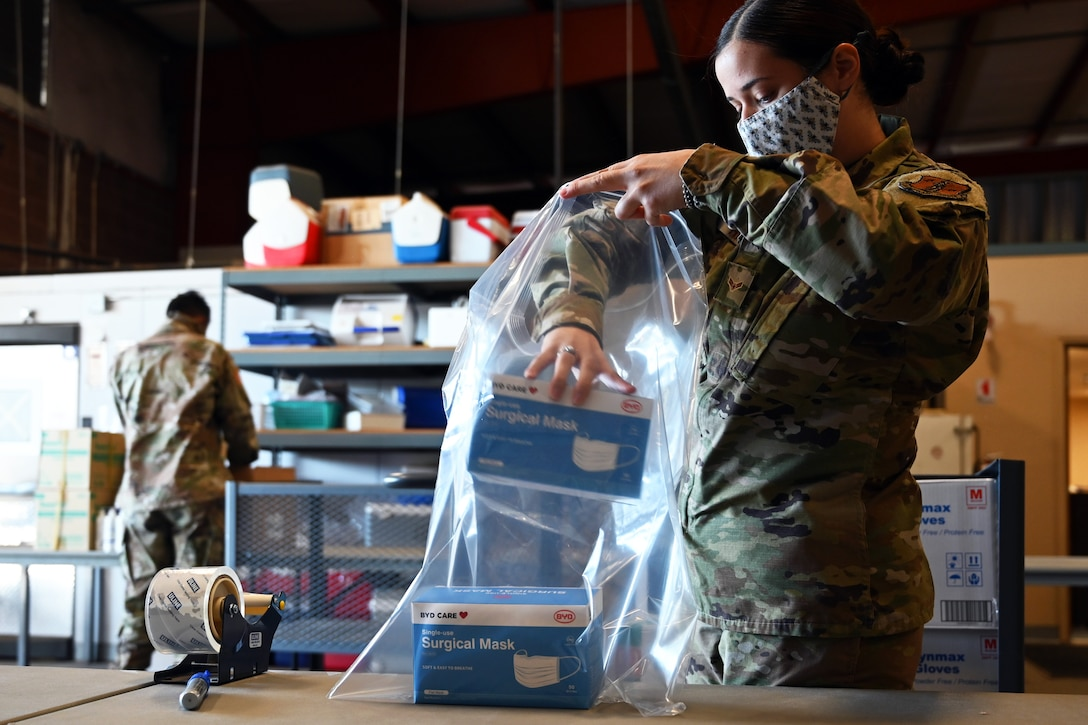 An airman wearing a face mask puts boxes that are labeled surgical masks into a large plastic bag.
