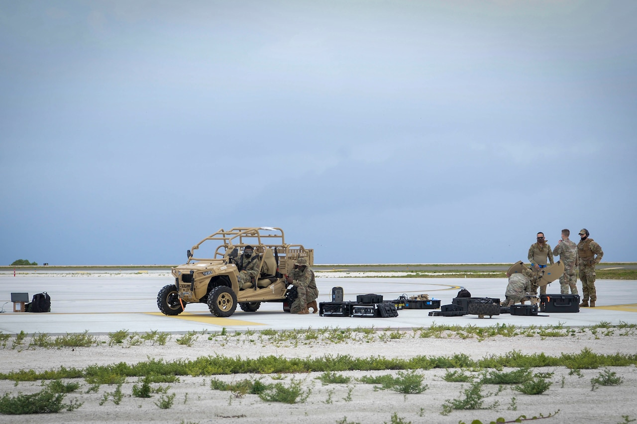 A vehicle and equipment is scattered about with troops milling nearby.