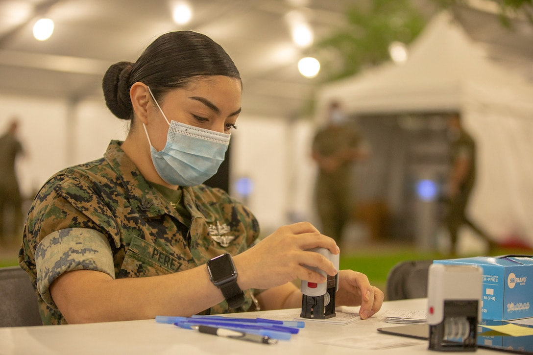 U.S. Navy Hospital Corpsman 3rd Class Dora Perez assigned to 2d Marine Division, Camp Lejeune, North Carolina, prepares vaccination cards at the Memphis Community Vaccination Center in Memphis, Tennessee, April 16, 2021.