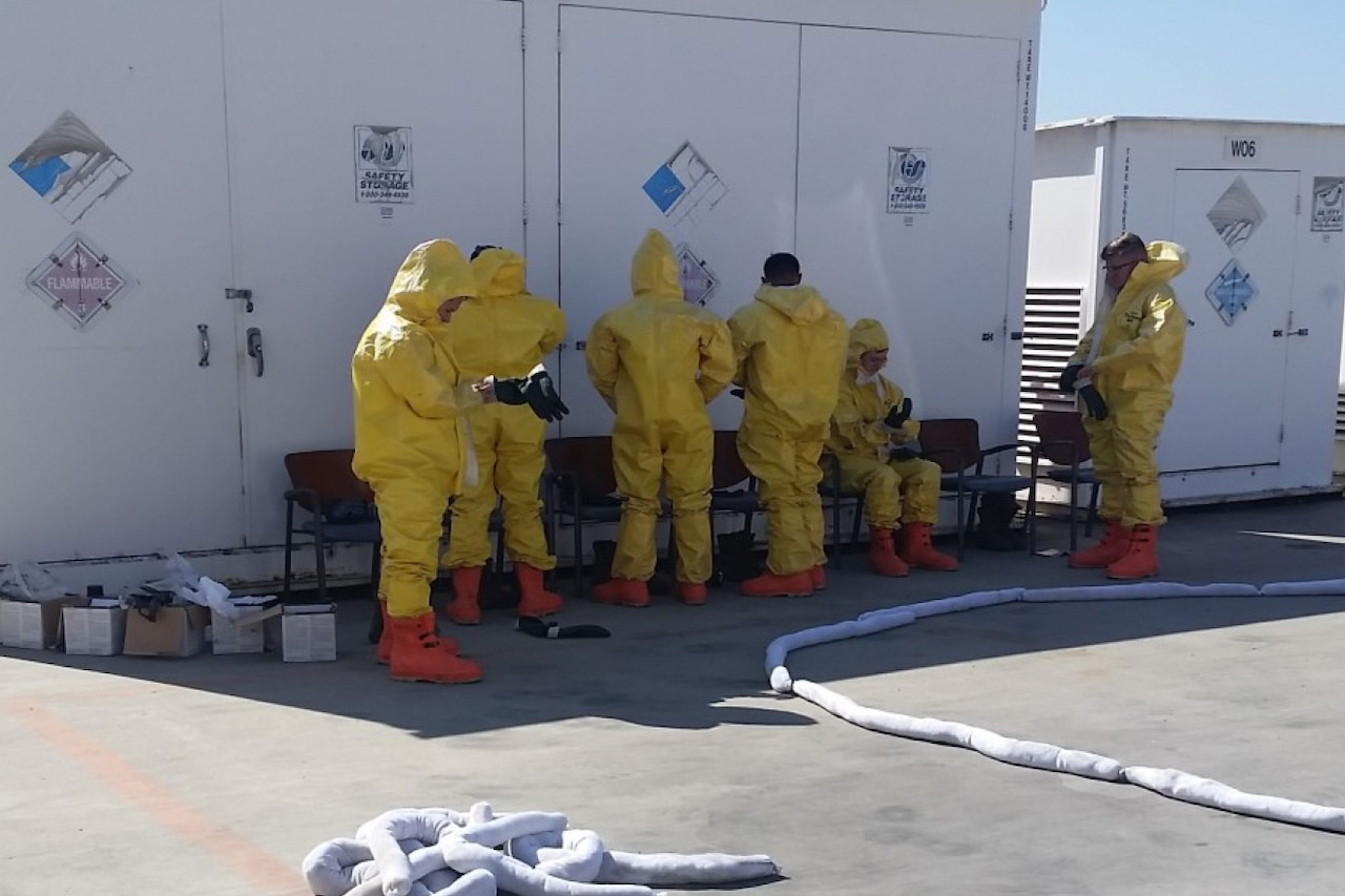 People put on hazardous materials suits.