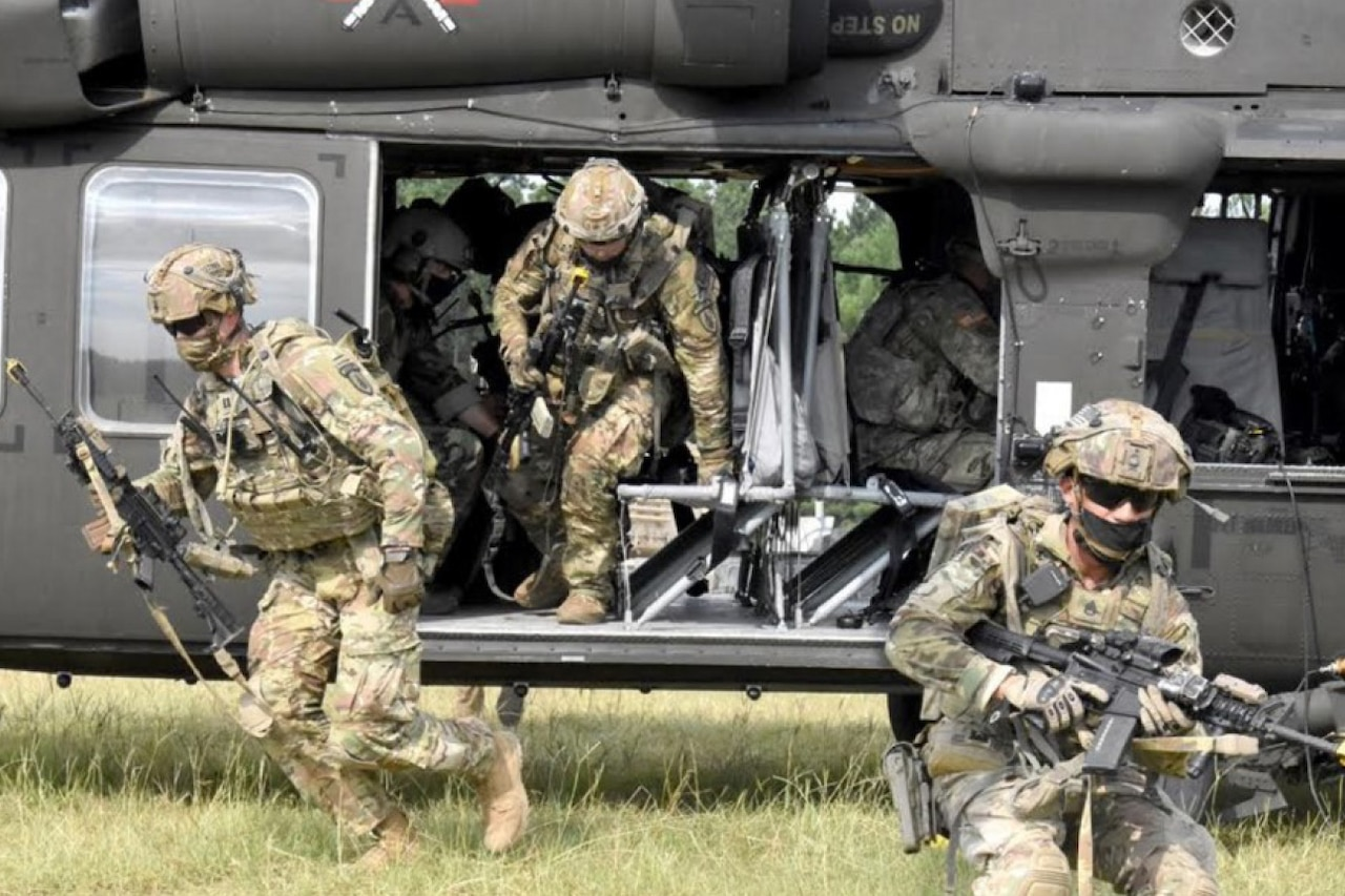 Soldiers exit a helicopter.