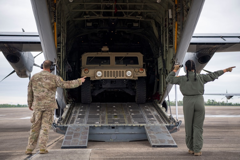 A humvee is loaded onto a C-130J