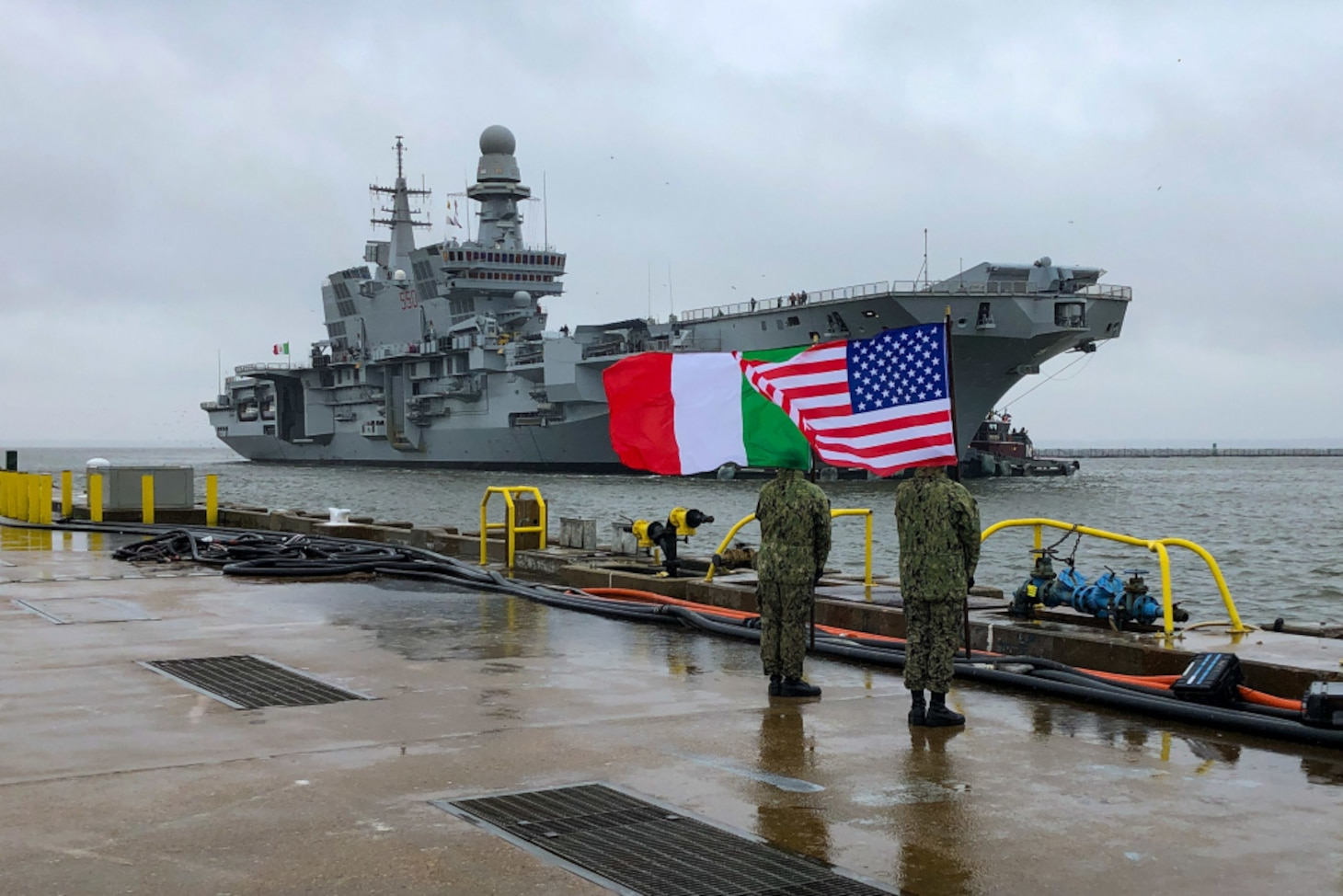 "U.S. Sailors, assigned to the aircraft carrier USS John C. Stennis (CVN 74), greet the Italian Navy flagship, aircraft carrier ITS Cavour (CVH 550), as it arrives at Naval Station Norfolk, Virginia, Feb. 13, 2021. The Cavour's visit is part of a series of operations alongside U.S. military assets to attain the Italian Navy's ""Ready for Operations"" certification to safely land and launch F-35B aircraft, U.S. 2nd Fleet exercises operational authorities over assigned ships, and landing forces on the East Coast and the Atlantic."