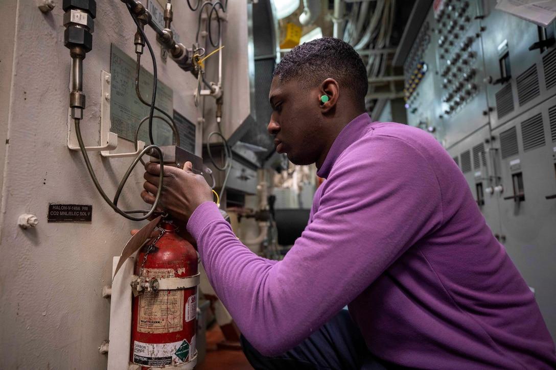 A sailor performs maintenance on a ship.