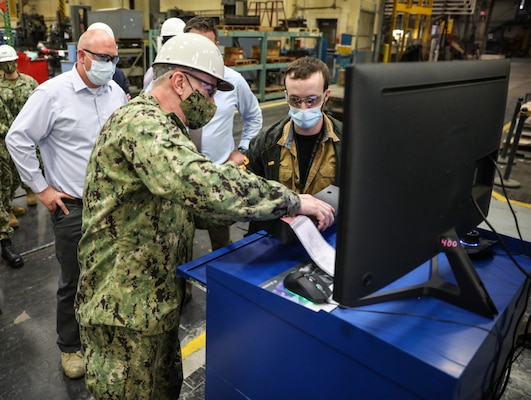 Adm. William Lescher, Vice Chief of Naval Operations, discusses Computerized Numerical Control (CNC) machines with Inside Shop Marine Machinists Work Leader, Patrick Phelps, during a visit to Norfolk Naval Shipyard (NNSY).