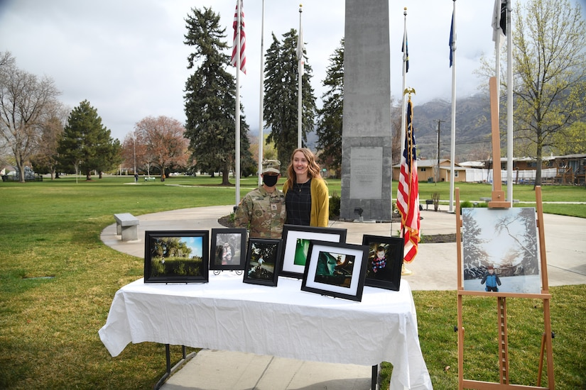A female Soldier and a woman pose for a picture in front of photos