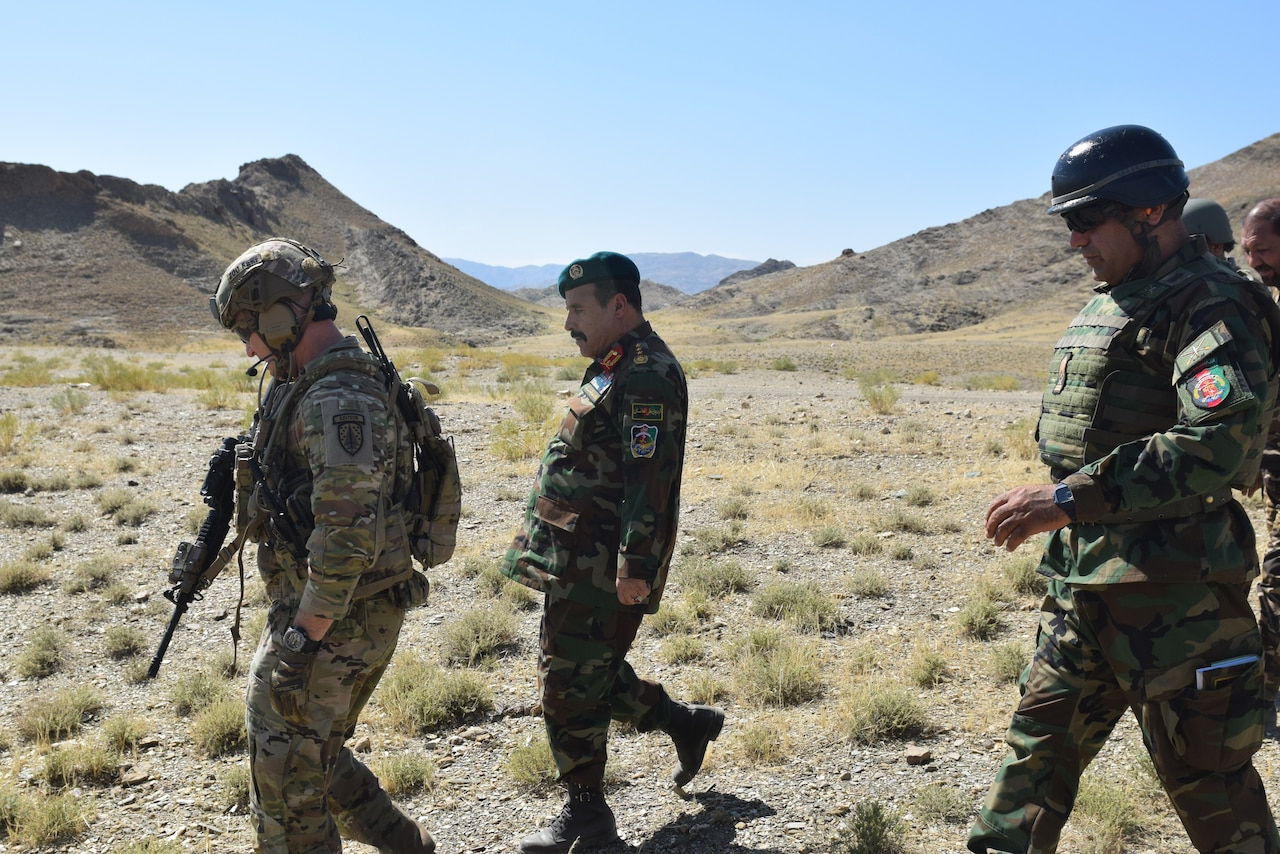 An American soldier and Afghanistan military personnel walk together across a rugged terrain.